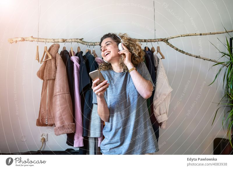 Young woman listening music in her bedroom fashion clothing clothes fashionable rack choosing retail store shop sale hanger customer style shopper shopaholic