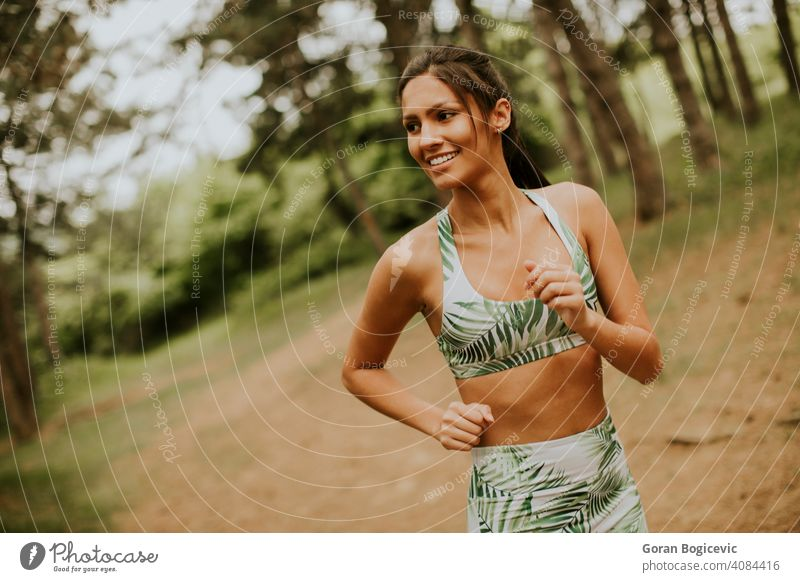 Young fitness woman running at forest trail female athlete park active green exercise young outdoor runner jogging training jogger tree lifestyle sport rural