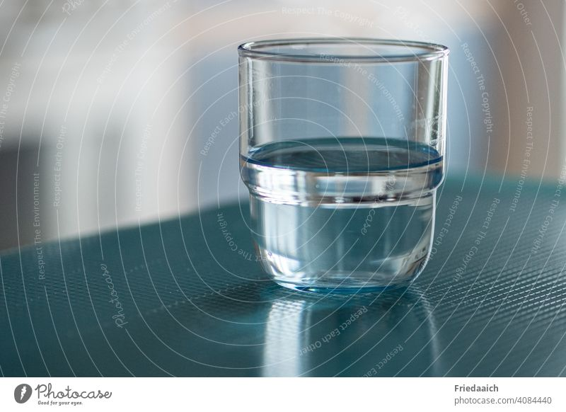 Water glass half full or half empty Glass Beverage Fluid Blue at home Drinking Minimalistic Visual spectacle blurred background Frontal Close-up