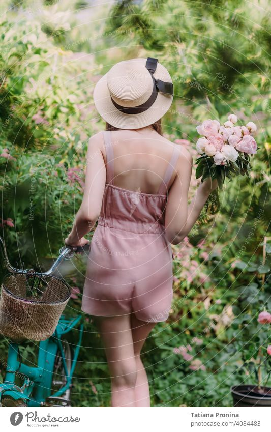 Stylish girl in a straw hat and a pale pink powdery jumpsuit walks with a mint-colored Bicycle in the garden of a country house. She holds a bouquet of fresh pink peonies in her hands. Stands with his back to the camera