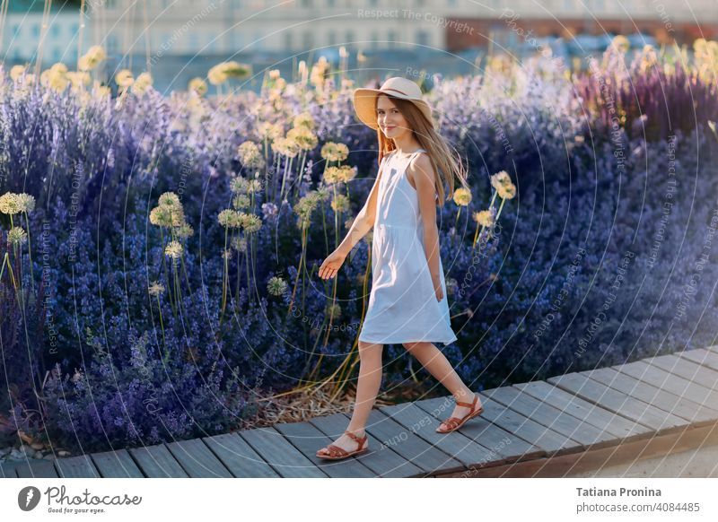 Smiling little girl in white dress and hat walk in lavender city park childhood violet summer sun cute kid toddler smile happy fun play lifestyle people purple