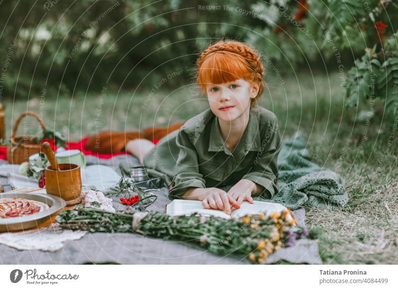 Red-haired little girl read book at retro picnic outdoor vintage hairstyle dress story tale study positive garden pretty reading blanket toddler life rest
