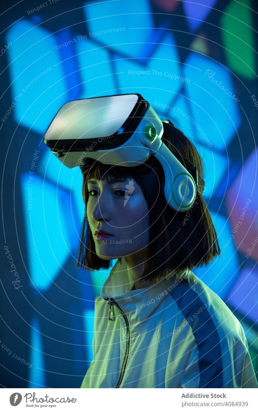 Woman in VR headset woman vr virtual reality technology neon light touching device digital innovation young person glasses asian modern entertainment game