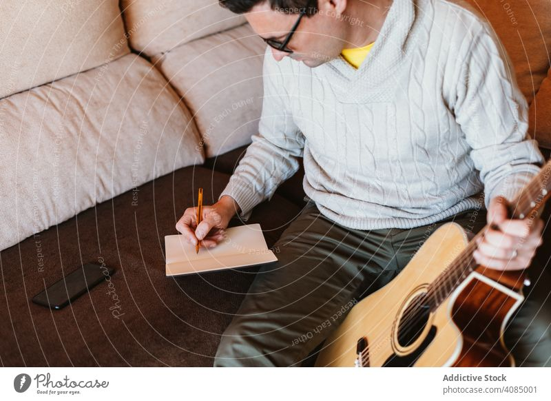 Musician writing in a notebook guitar musician acoustic student apartment pencil home man hand space young play entertainment guy instrument musical guitarist