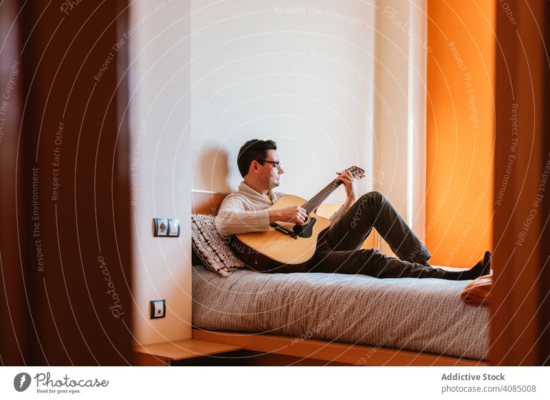 Man playing the guitar on the bed man music sitting home bedroom person male instrument musician young people caucasian using house rock indoors apartment