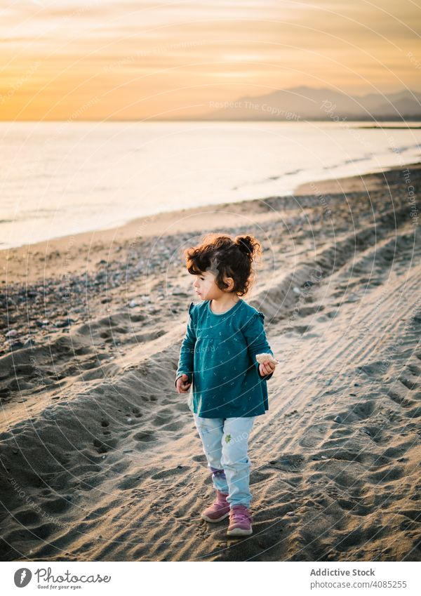 little girl looking at sea beach view freedom adorable summer ocean standing kids sand water travel white beautiful child vacation blue caucasian outdoor young