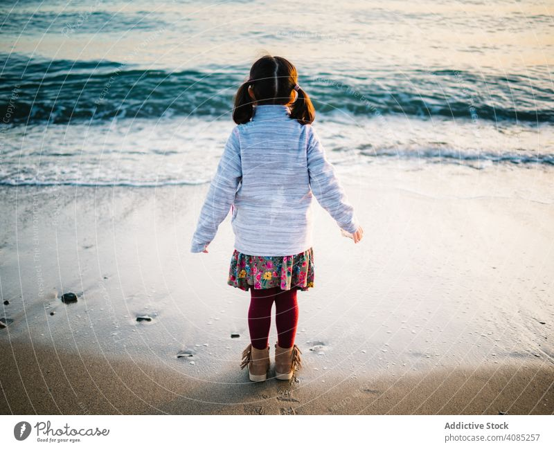 back view of little girl looking at sea beach freedom adorable summer ocean standing kids sand water travel white beautiful child vacation blue caucasian