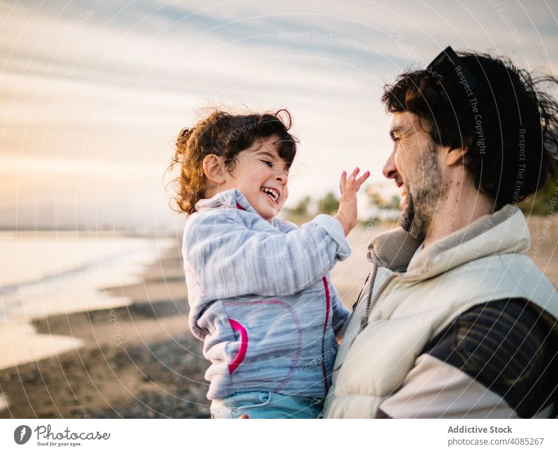 father holding little daughter at the beach hug ocean dad lifestyle happiness child love day girl fun caucasian male cute kid female playing sea outside happy
