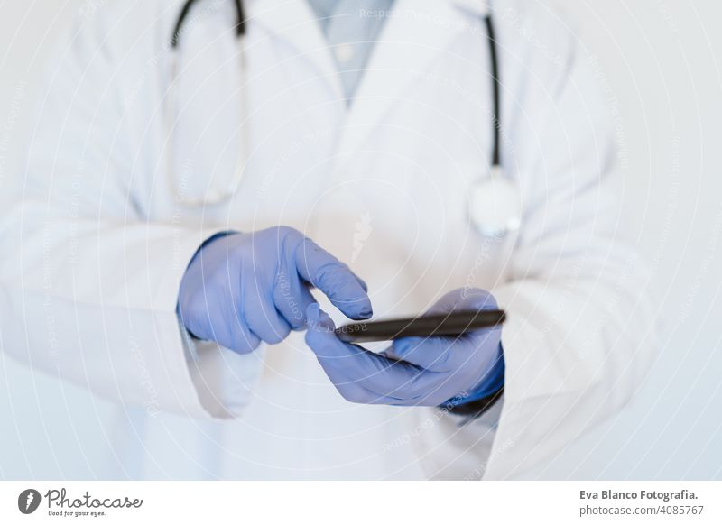 unrecognizable doctor wearing protective mask and gloves indoors using mobile phone. Corona virus concept technology internet wireless man professional