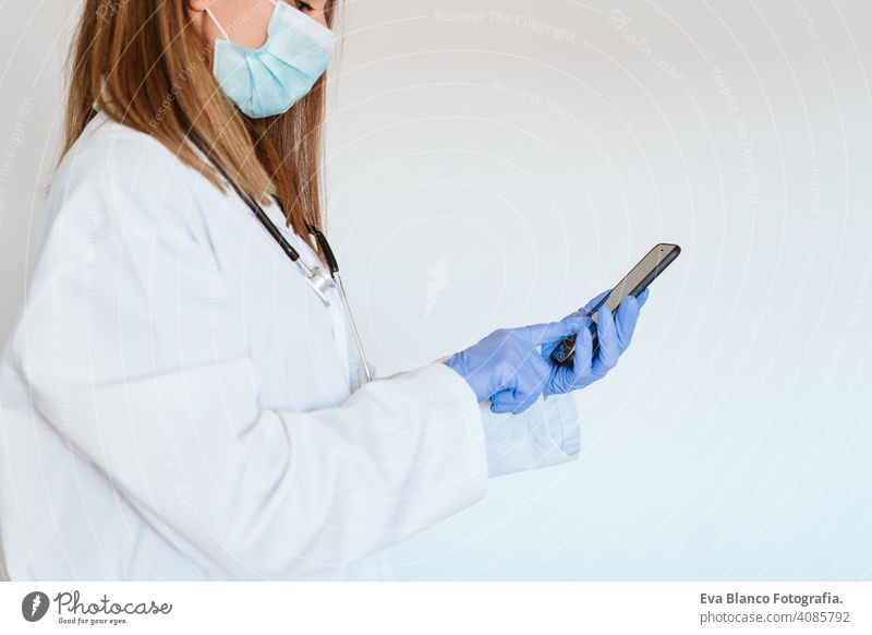 portrait of doctor woman wearing protective mask and gloves indoors. Using mobile phone. Corona virus concept technology internet wireless cloe up professional
