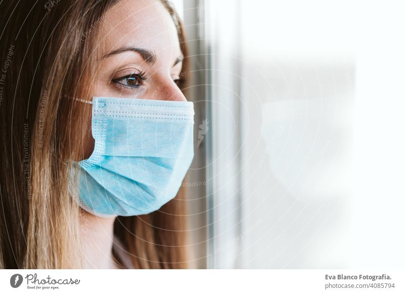 portrait by the window of doctor woman wearing protective mask and gloves indoors. Corona virus concept stop hand professional corona virus hospital working