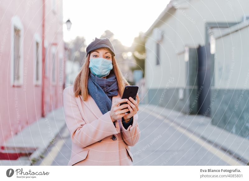 caucasian woman in the street wearing protective mask and using mobile phone. corona virus concept outdoors technology internet public adult infection space