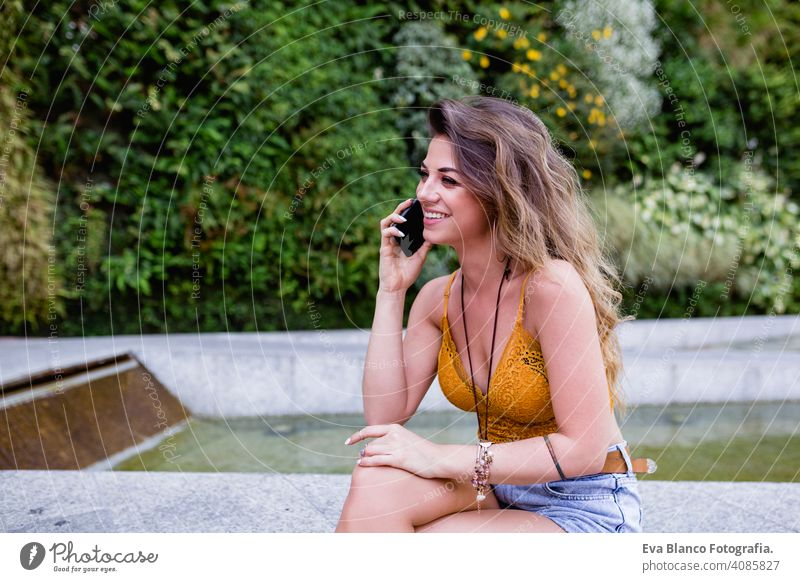 young blonde beautiful woman at the street talking on mobile phone and smiling. Lifestyle outdoors. Summertime smart call urban happy people run modern late