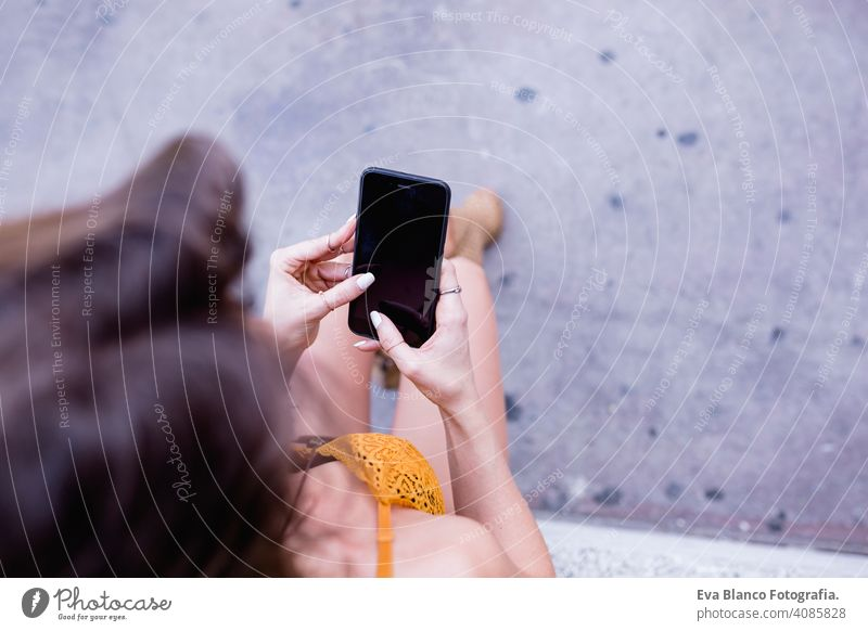 young blonde beautiful woman at the street using mobile phone and smiling. Lifestyle outdoors. Summertime, Green background smart urban happy people run modern