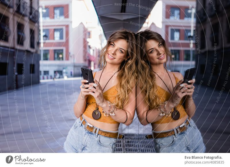 young blonde beautiful woman at the street using mobile phone. Glass reflection. Lifestyle outdoors. Summertime. smart call urban happy people smiling run