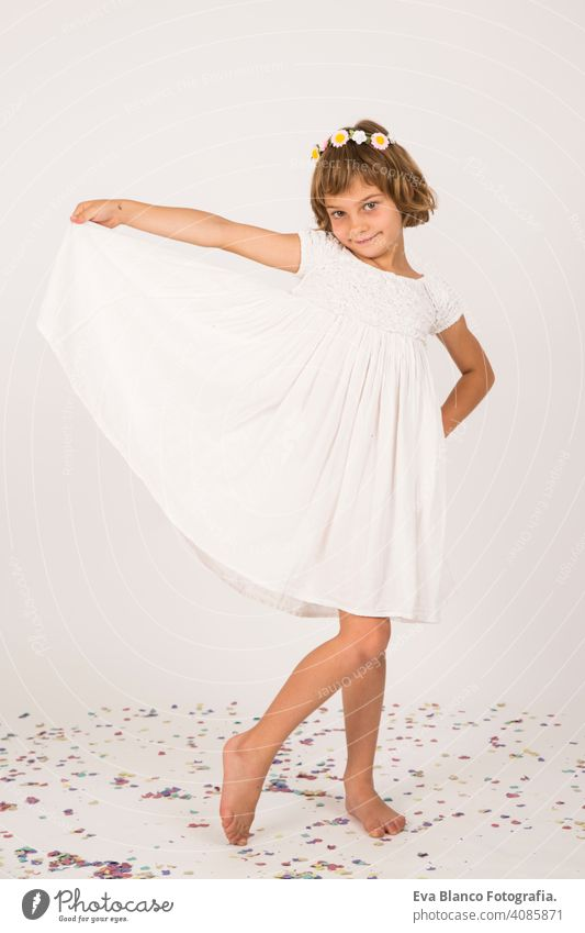 indoor portrait of a kid having fun. confetti on the floor. white dress on little girl portrait. indoors, confetti on the floor. white  background child cute