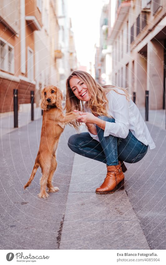 young woman at the street hugging her cute cocker dog. Lifestyle outdoors with pets walking city urban purebred caucasian coker lifestyle friendship beautiful