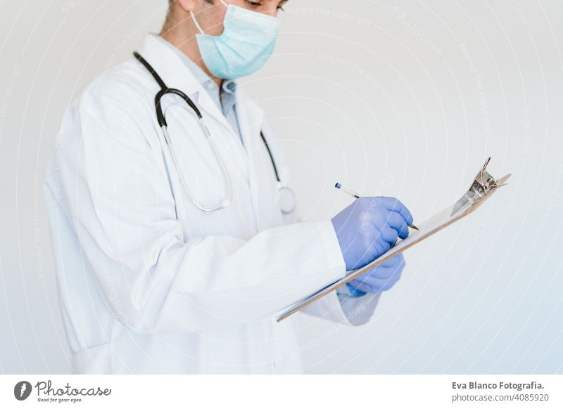 portrait of caucasian doctor using protective gloves and mask. Working on a folder. Chinese Corona virus concept. 2019-nCoV man professional corona virus