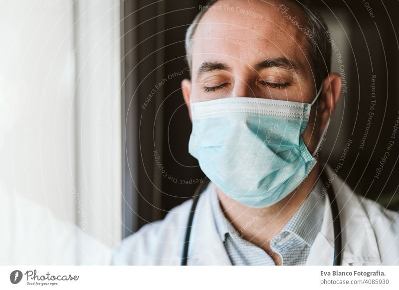 portrait of doctor man by the window wearing protective mask and gloves indoors. Corona virus concept professional corona virus hospital working infection