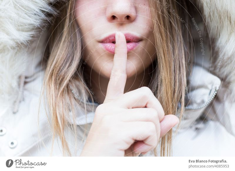 silence, gesture and beauty concept - close up portrait of a young woman holding finger on lips happy beautiful girl lifestyle fashion coat nature park