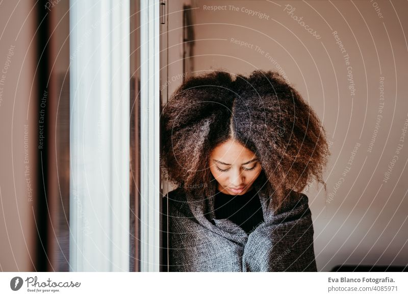 portrait of beautiful afro american young woman by the window. Lifestyle indoors coffee home ethnic mixed race tea autumn winter blanket daytime african smiling