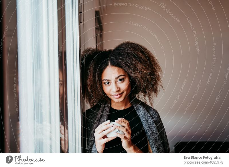 portrait of beautiful afro american young woman by the window holding a cup of coffee. Lifestyle indoors home ethnic mixed race tea autumn winter blanket