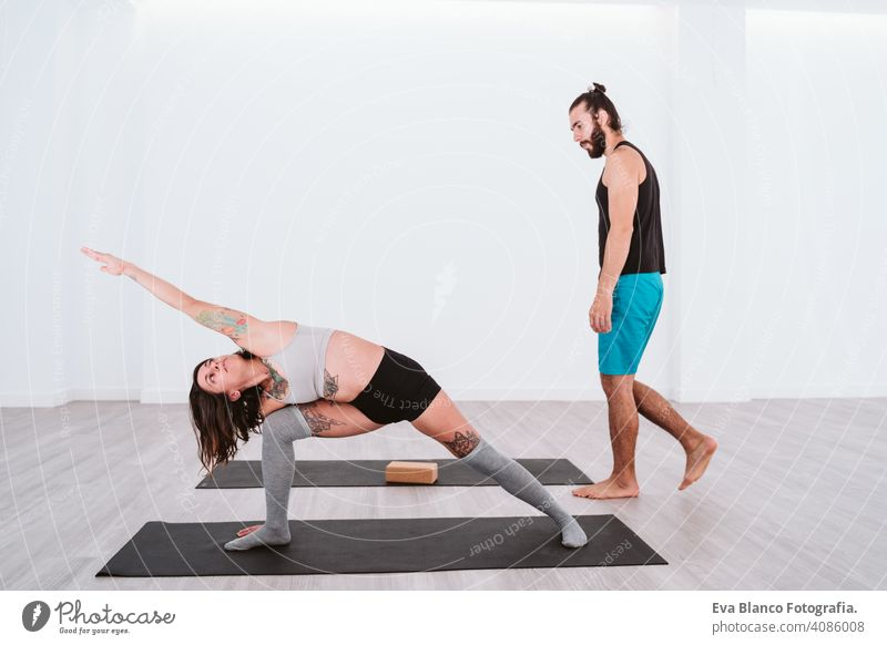 young man and woman practicing yoga sport at the gym. Healthy lifestyle boy health healthy indoors studio white hispanic sportive power professional male person