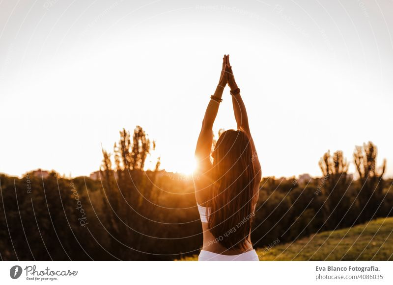 young beautiful asian woman doing yoga in a park at sunset. Yoga and healthy lifestyle concept summer happy enjoyment sport sportive relax relaxation field