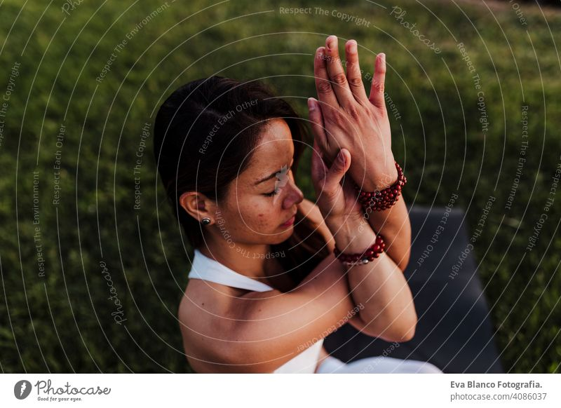 young beautiful asian woman doing yoga in a park at sunset. Yoga and healthy lifestyle concept. summer happy enjoyment sport sportive relax relaxation field