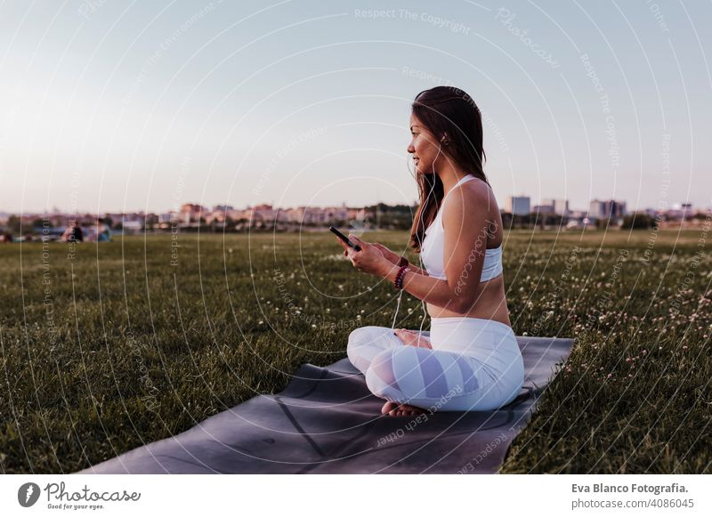 young beautiful asian woman relaxed after her yoga practice listening to music on earphones and mobile phone. Yoga and healthy life concept summer happy
