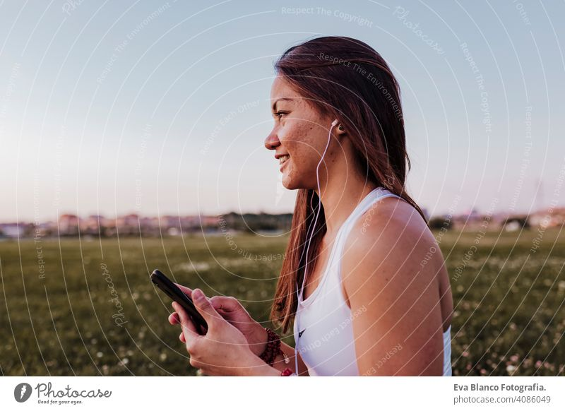 young beautiful asian woman relaxed after her yoga practice listening to music on earphones and mobile phone. Yoga and healthy lifestyle concept summer happy