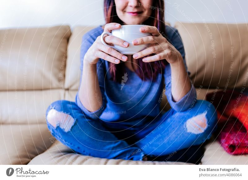 young caucasian woman having coffee or tea at home for breakfast at home. Close up view living resting lifestyle leisure indoors person sitting hot smiling
