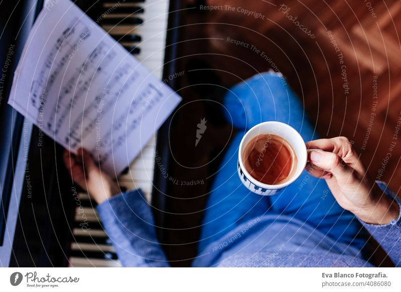 young unrecognizable woman holding a cup of coffee and playing piano by reading a music sheet. Music concept indoors. top view style human key note lesson