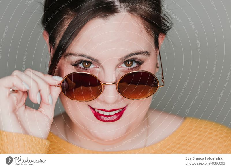 young woman close up portrait with sunglasses smiling. led ring reflection in the eyes. Real woman concept fashion glamor mouth caucasian makeup femininity