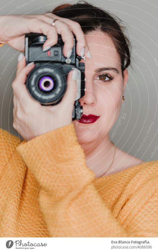 close up portrait of a young woman holding a camera. Photography concept casual attractive happy photographer paparazzi professional photography lens modern art