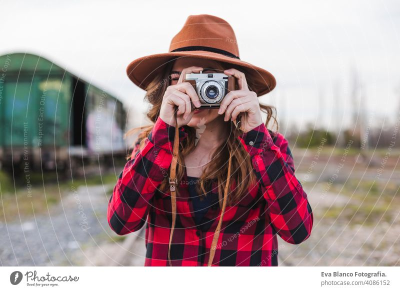 young beautiful woman wearing casual clothes and a hipster hat taking a picture with a vintage camera. Outdoors city background. Lifestyle. happy photo adult