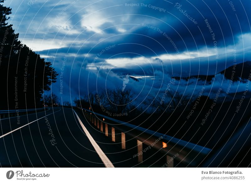 inside view from the car of a cloudy sunset while driving. winter season velocity dashboard panoramic mirror vehicle mountain transport auto horizontal blue