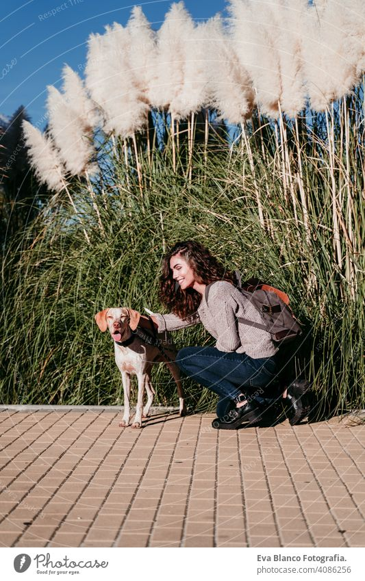 young woman and her dog outdoors in a park. sunny day, autumn season love pet owner beautiful happy smile mixed race purebred breed hug backpack walking