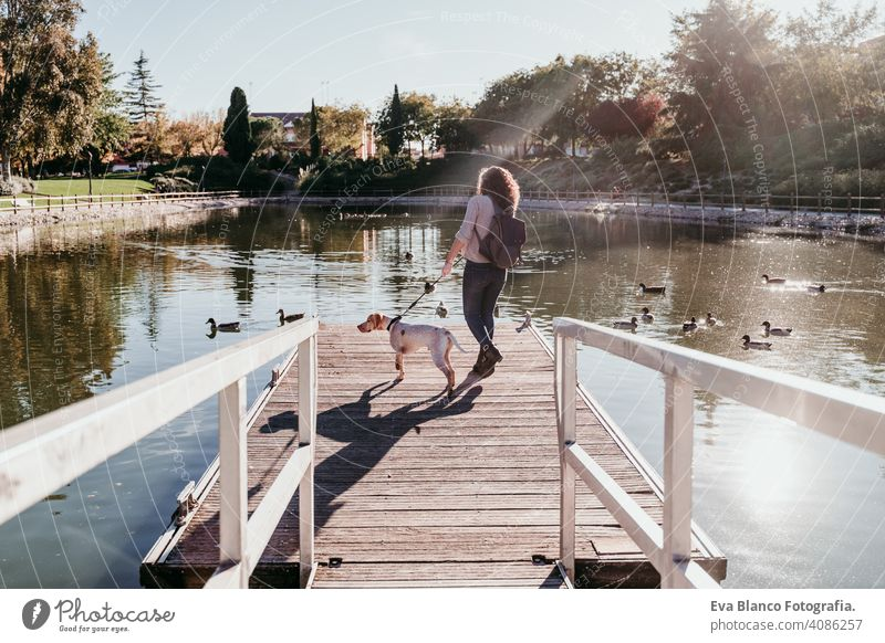 young woman and her dog outdoors in a park with a lake. sunny day, autumn season love pet owner beautiful happy smile mixed race purebred breed hug backpack