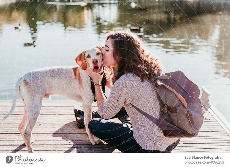 young woman kissing her dog outdoors in a park with a lake. sunny day, autumn season love pet owner beautiful happy smile mixed race purebred breed hug backpack