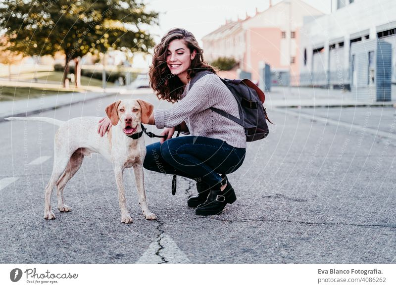 young woman and her dog outdoors walking by the street. autumn season park love pet owner sunny beautiful happy smile mixed race purebred breed hug backpack