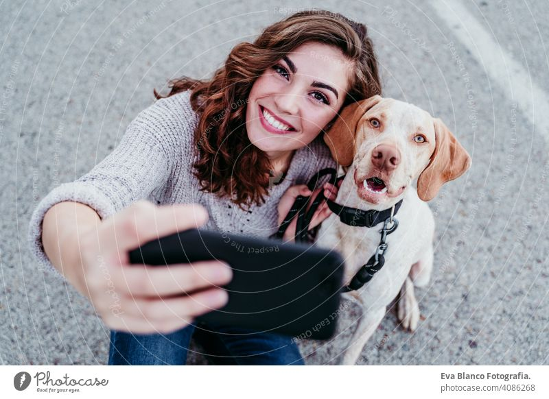 young woman taking a selfie with mobile phone with her dog at the street. autumn season picture photo technology park outdoors love pet owner sunny beautiful