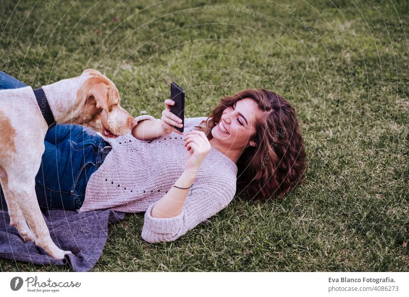 young woman taking a selfie with mobile phone with her dog at the park. autumn season picture photo technology outdoors love pet owner sunny beautiful happy