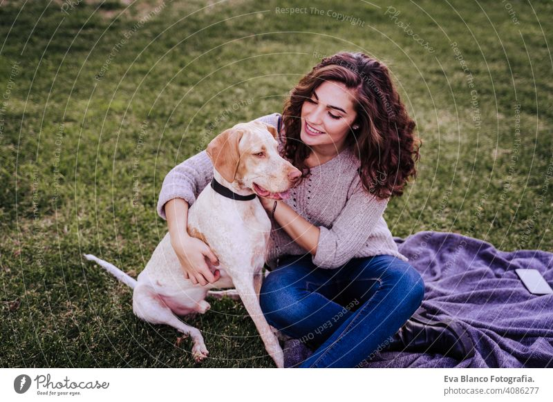 young woman taking a selfie with mobile phone with her dog at the park. autumn season portrait outdoors love pet owner sunny beautiful happy smile mixed race