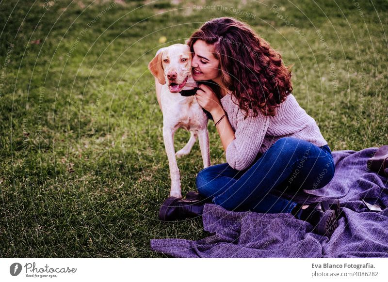 young woman with her dog at the park. she is hugging the dog. autumn season portrait outdoors love pet owner sunny beautiful happy smile mixed race purebred