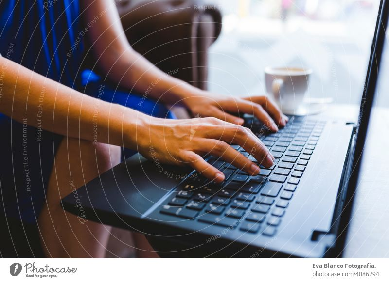 top view of a young beautiful woman writing on laptop, coffee besides. Casual blue dress. Modern life indoors hipster college computer display notebook looking