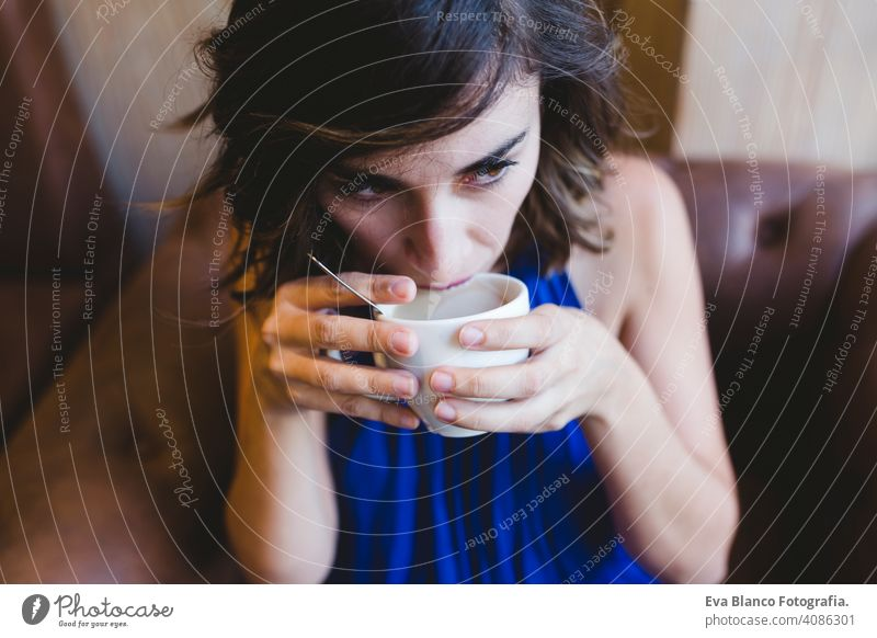 young beautiful woman enjoying a cup of coffee in a cafe. laptop besides. Casual blue dress. Modern life indoors morning holding beauty girl adult lovely joyful