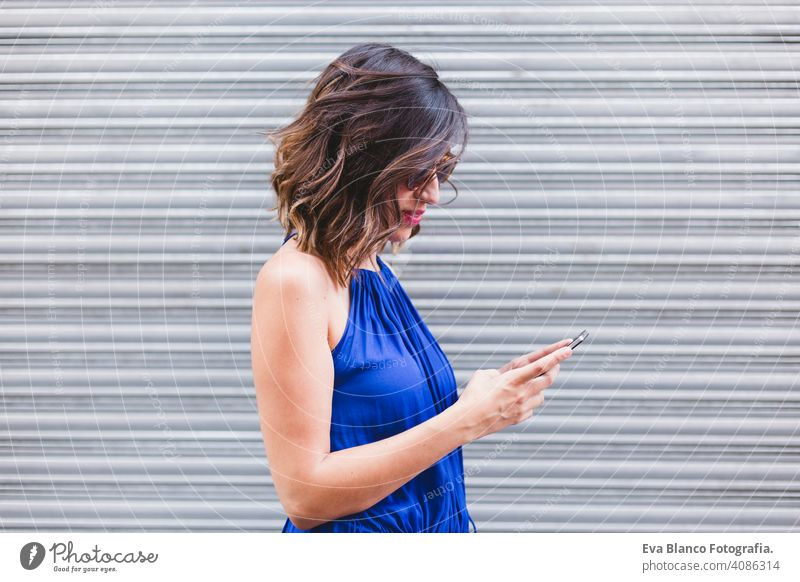 young beautiful woman using mobile phone and smiling. She is in the street, wearing a casual blue dress, sunglasses and smiling. LIfestyle outdoors, modern life and technology