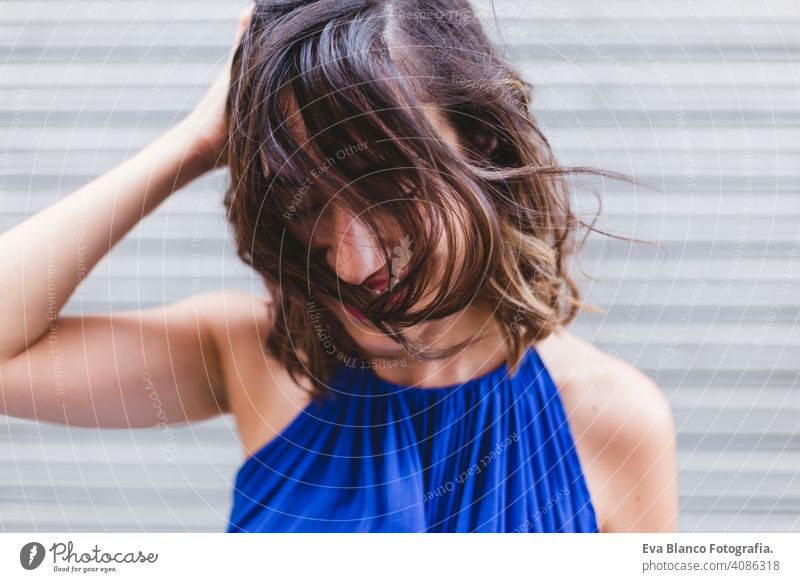 young beautiful woman smiling and playing with hair. She is in the street, wearing a casual blue dress. LIfestyle outdoors, modern life. positive stylish