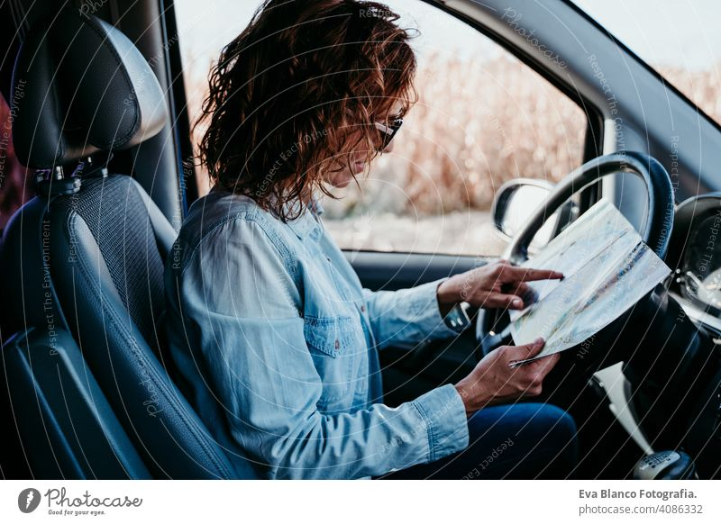 young beautiful woman reading a map in a car. travel concept driving sunny sunglasses traveling wheel drive hire sharing new traffic maintenance expensive